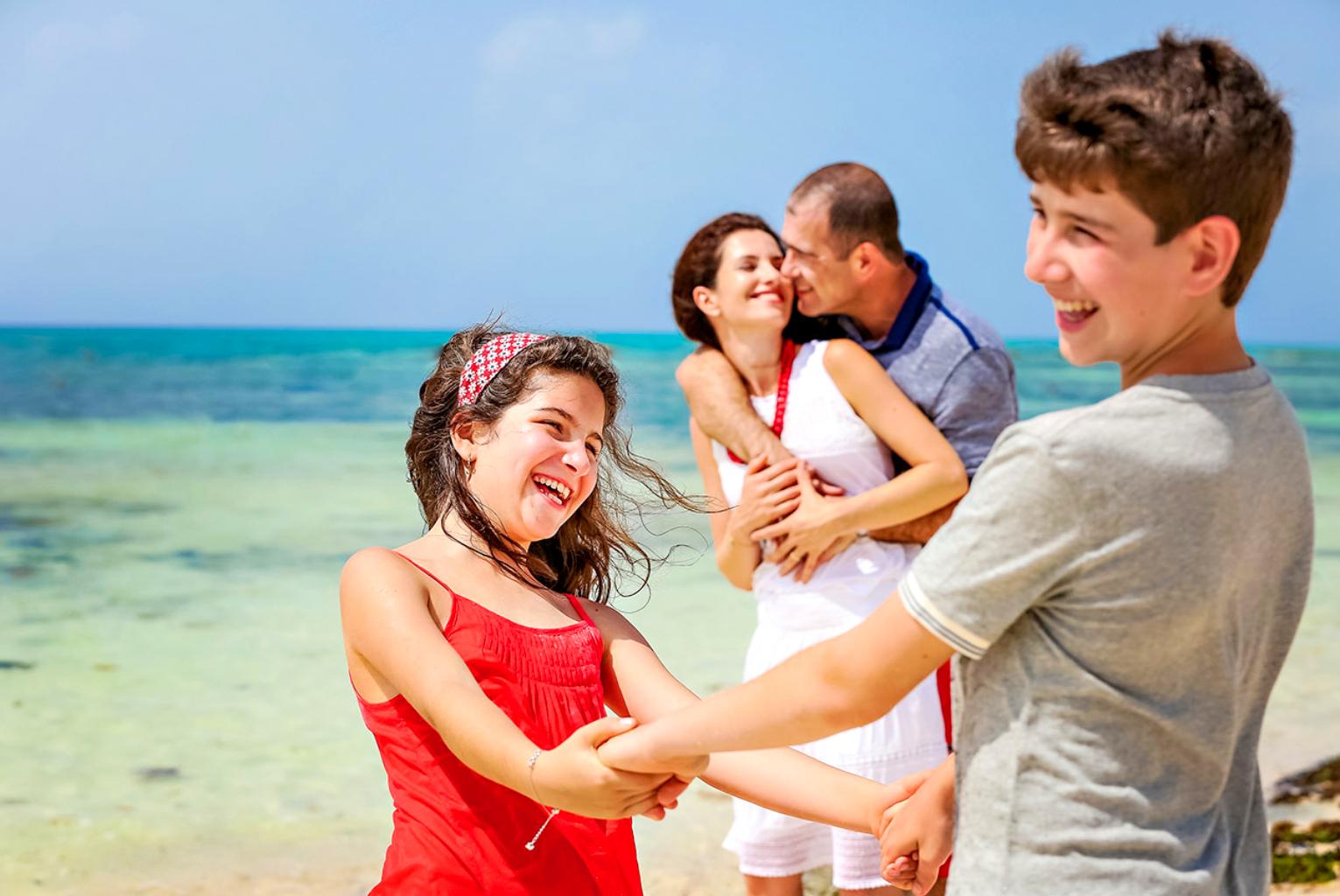 familia padres e hijos felices en la playa