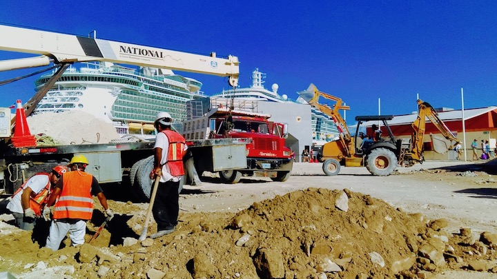 obra en construcción con hombres constructores y tractores, con cruceros de fondo