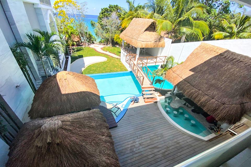 jardín con alberca y palapas frente al mar proyecto private paradise